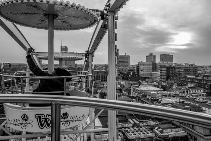 A person taking a selfie, while riding a ferris wheel.