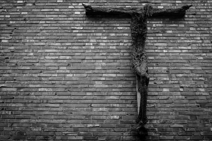 Wooden jesus statue on a brick wall