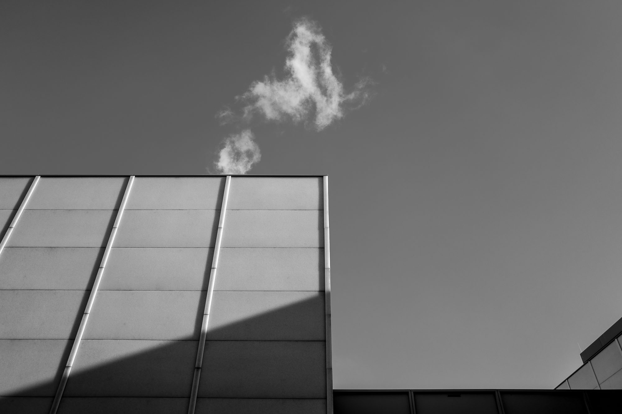 Rectangular building wall with a small cloud above it