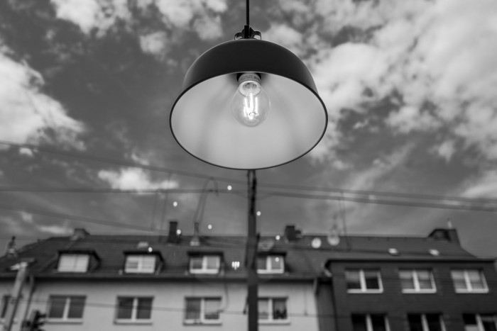 A lamp, with bright sky with clouds and some houses in the background
