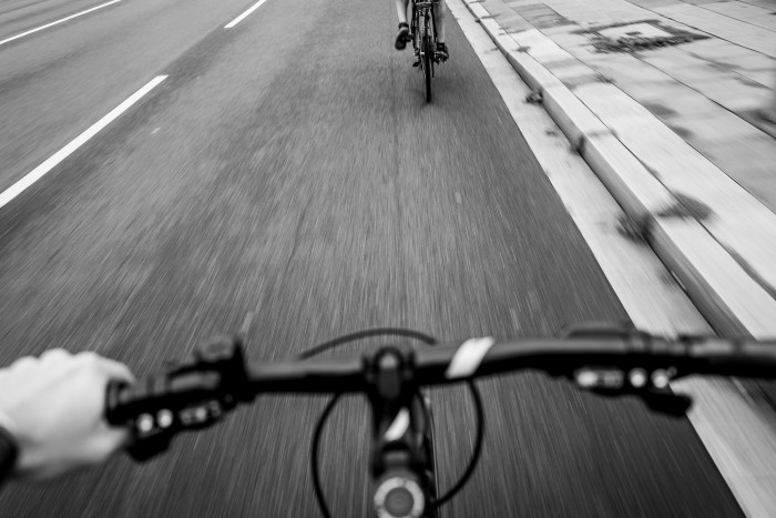 Handlebar in the foreground, street and another cyclist in the background
