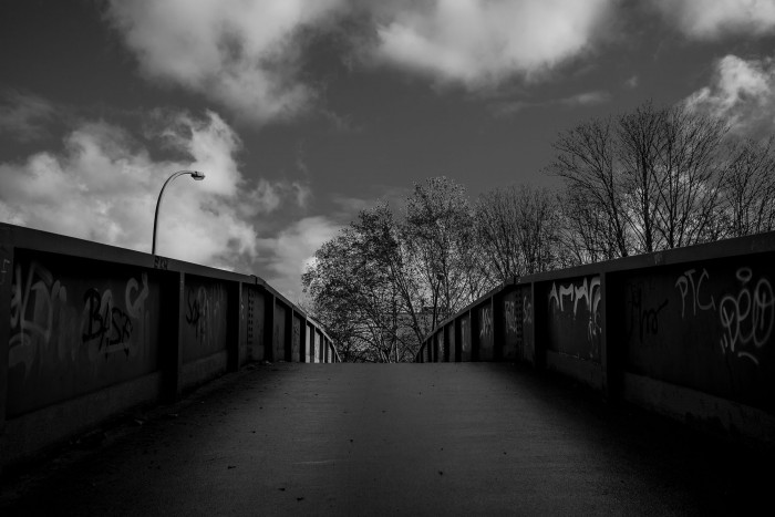 On a foot bridge, bright clouds and trees in the background