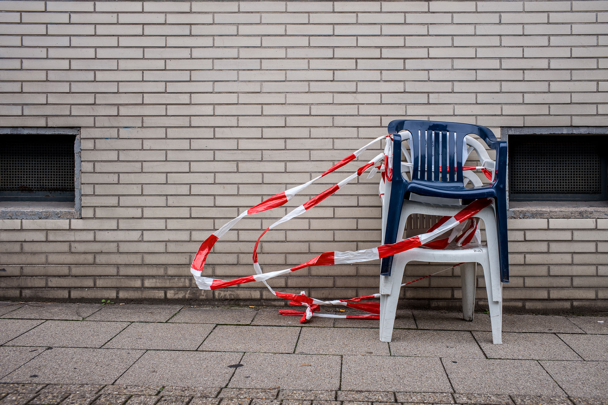 Stacked plastic chairs wrapped in barrier tape, that's blowing in the wind, a brick wall in the background