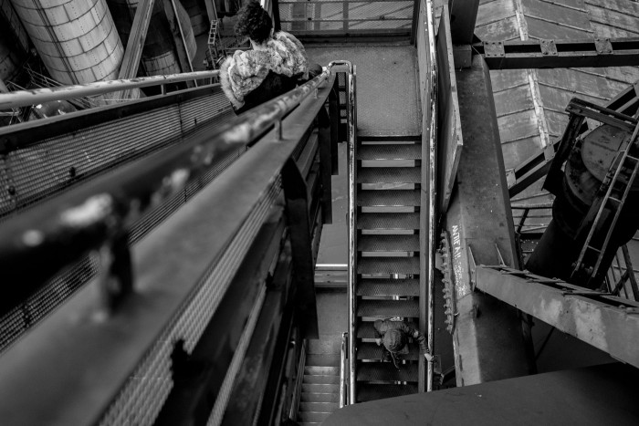 Two people are seen from above, going down a narrow staircase in a massive industrial structure