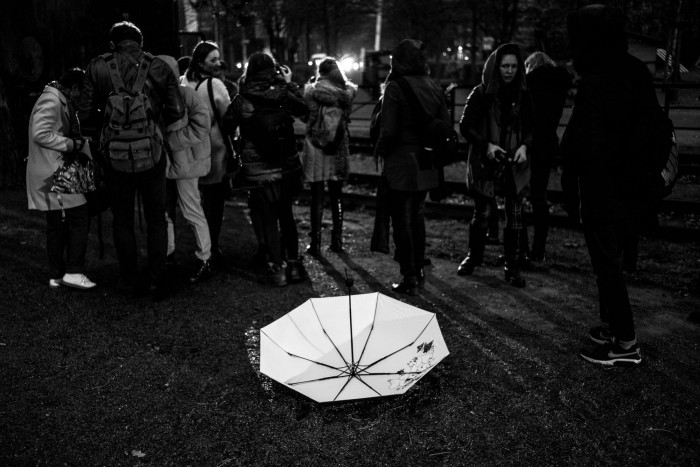 White, open umbrella, upside-down on dark ground, group of people in the background