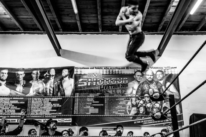 A wrestler, doing a cork screw from the top turnbuckle, mid-air, spectators around the ring, watching in awe