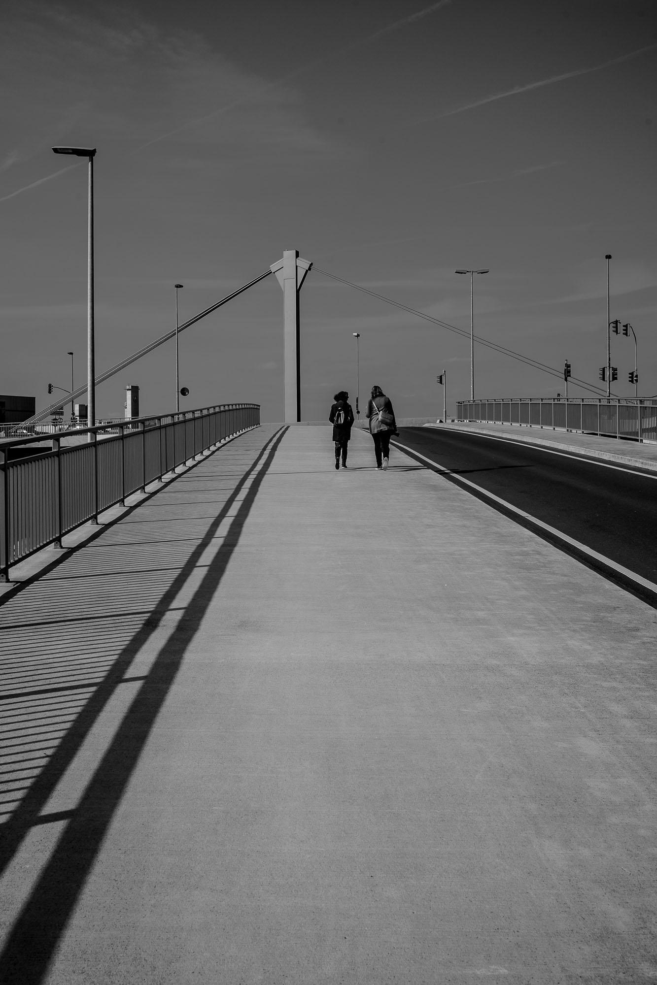 Two people walking up a bridge