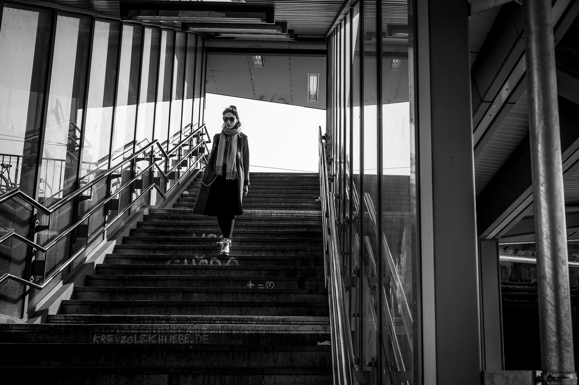 A woman walking down the stairs to the train platform