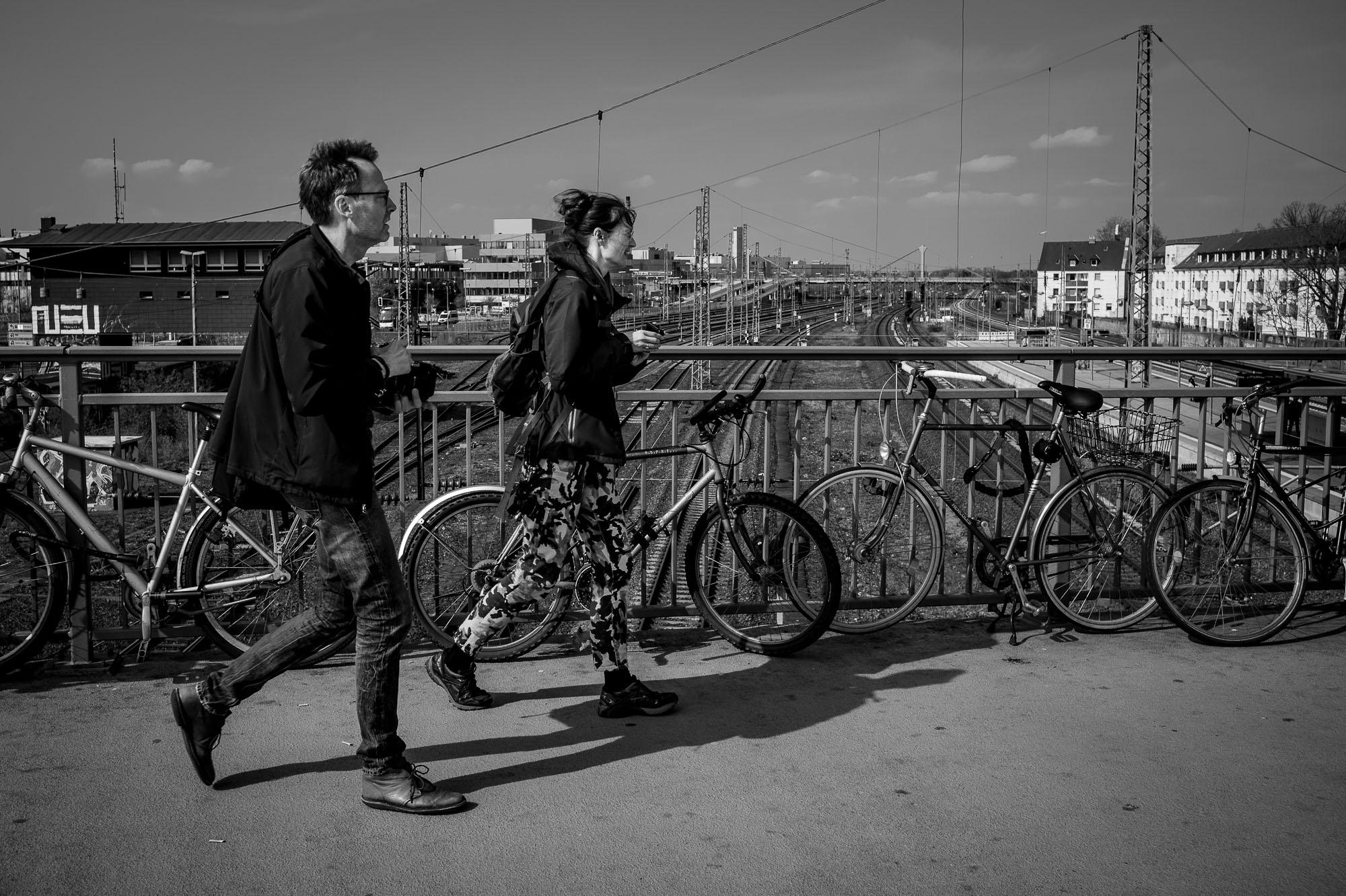 Photographers walking across a bridge above train tracks