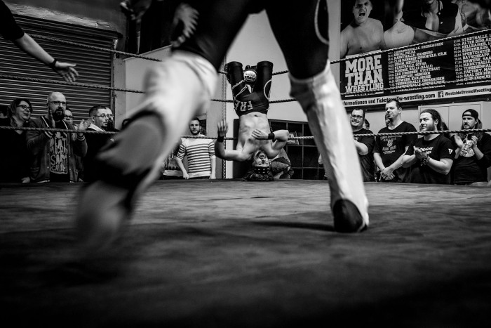 Wrestler Daniel Sparks charging at Fynn Freyhart who's hung up on the ropes