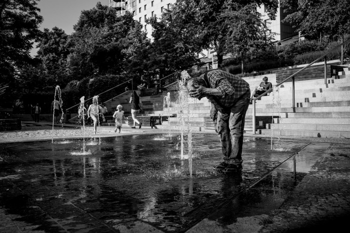 A man is cooling his head in a public fountain