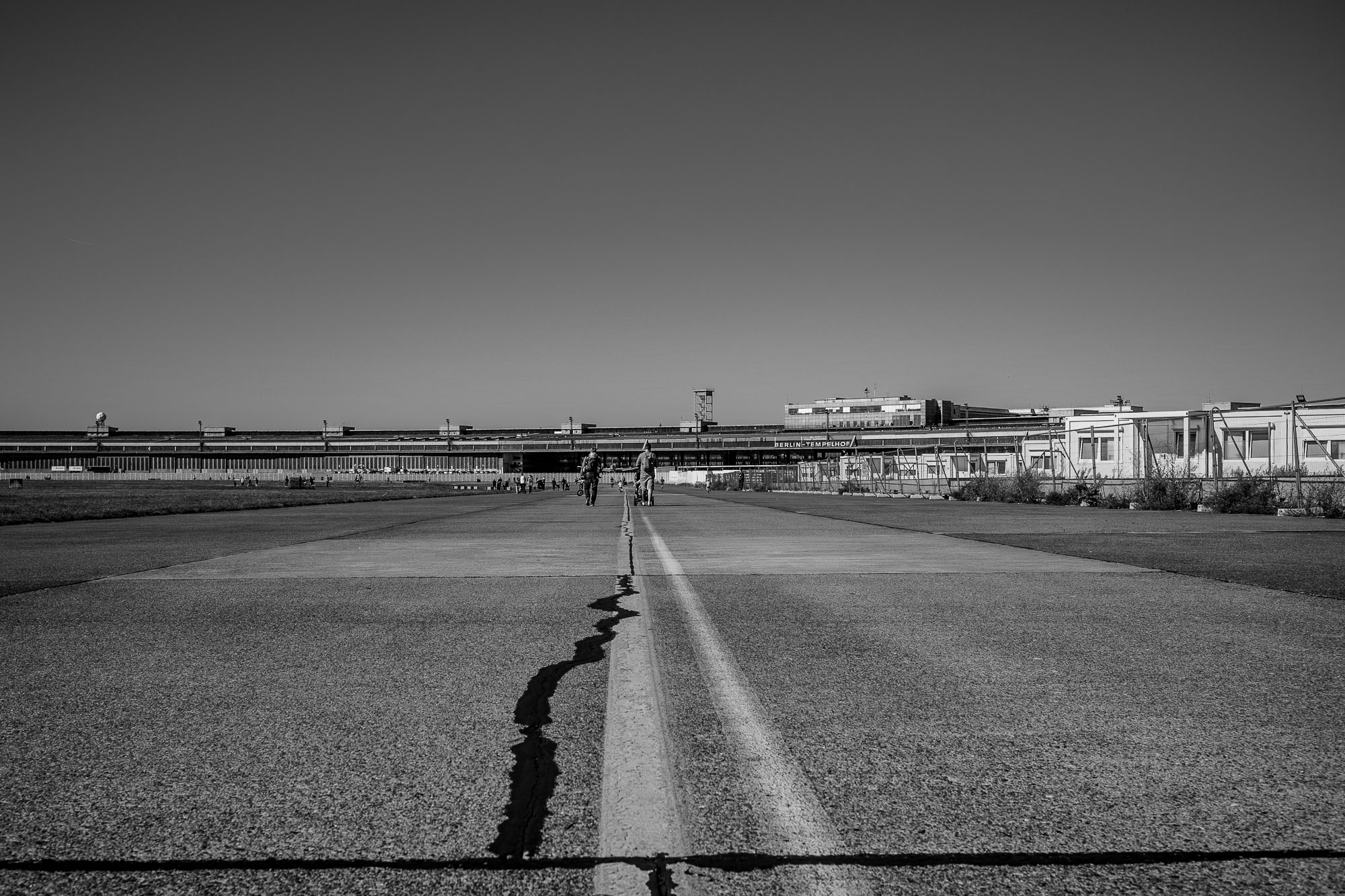 Tempelhof airport with people strolling towards it on the old tarmac