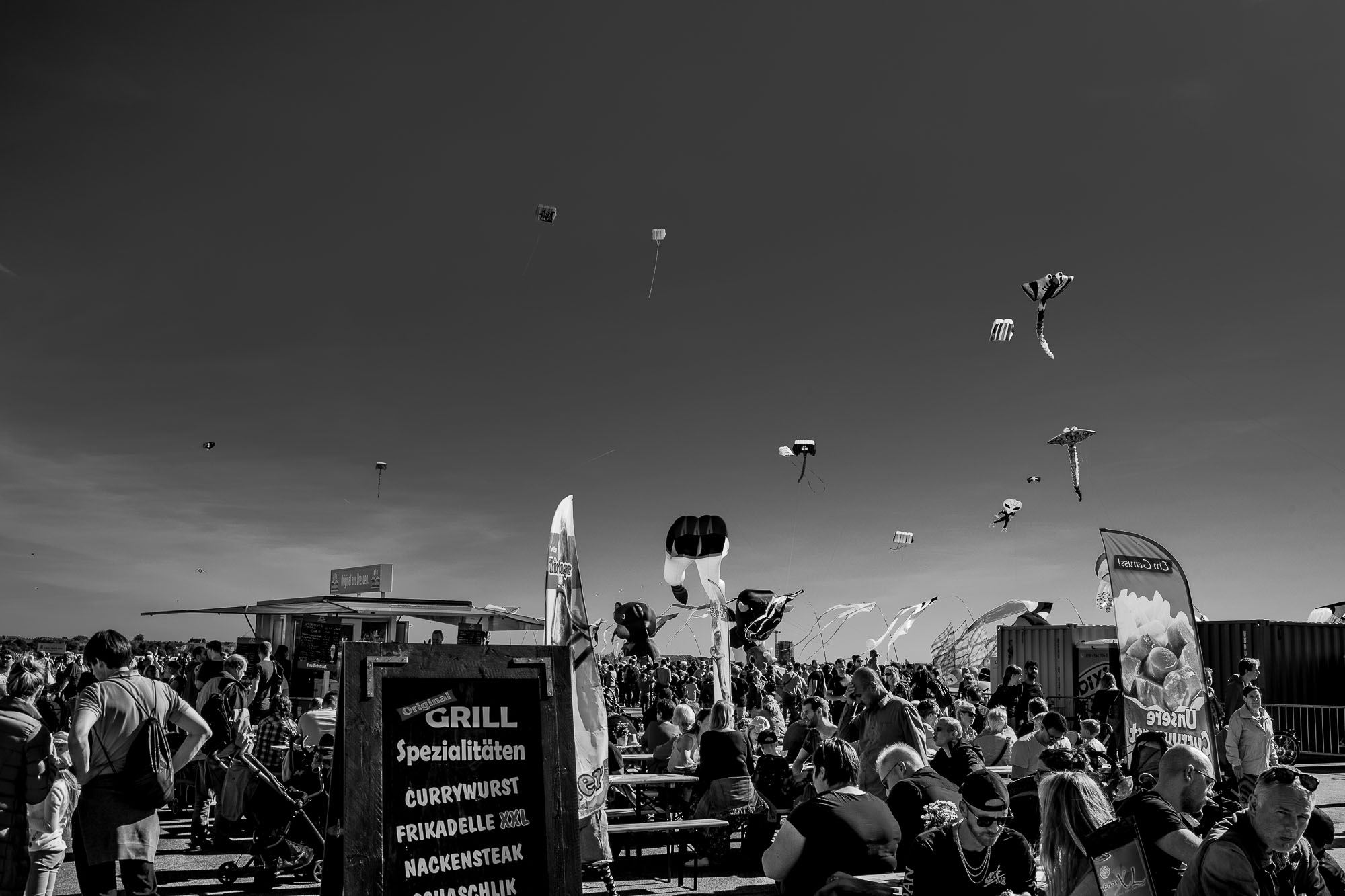 Kites in the sky above, people at tables having lunch below