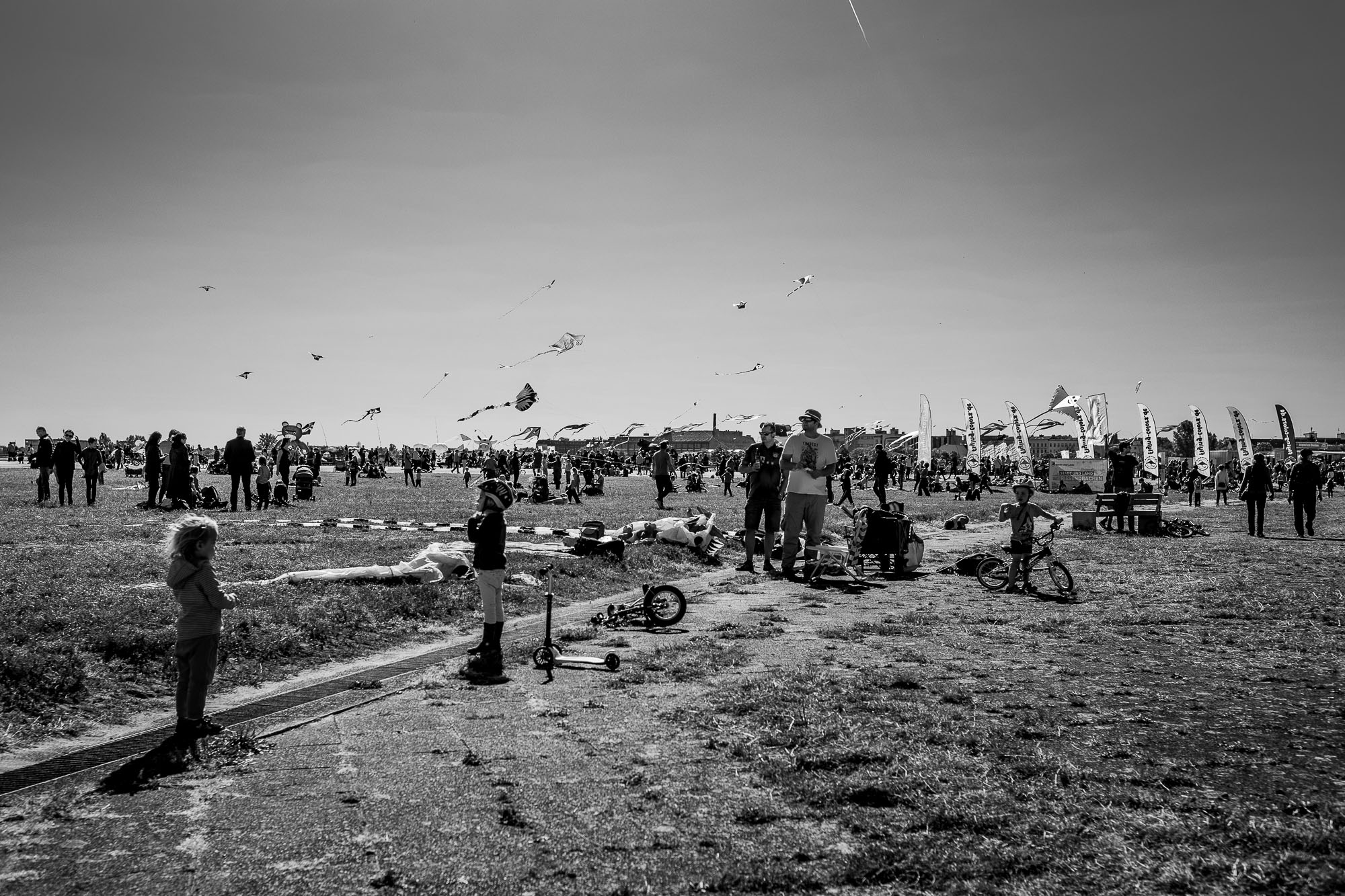 People at the Templehof Park watch a large number of kites in the sky