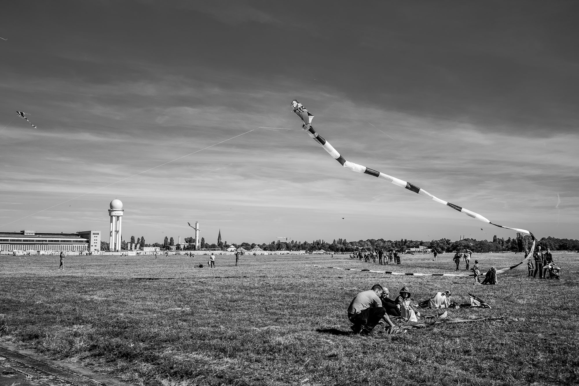 People sitting on the gras, watching a huge kite above them