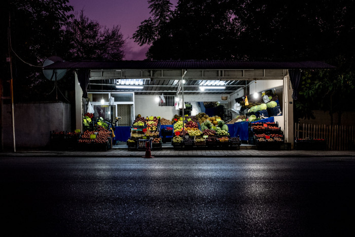 Fruit vendor at nightfall, with fluorescent lights illuminating the produce