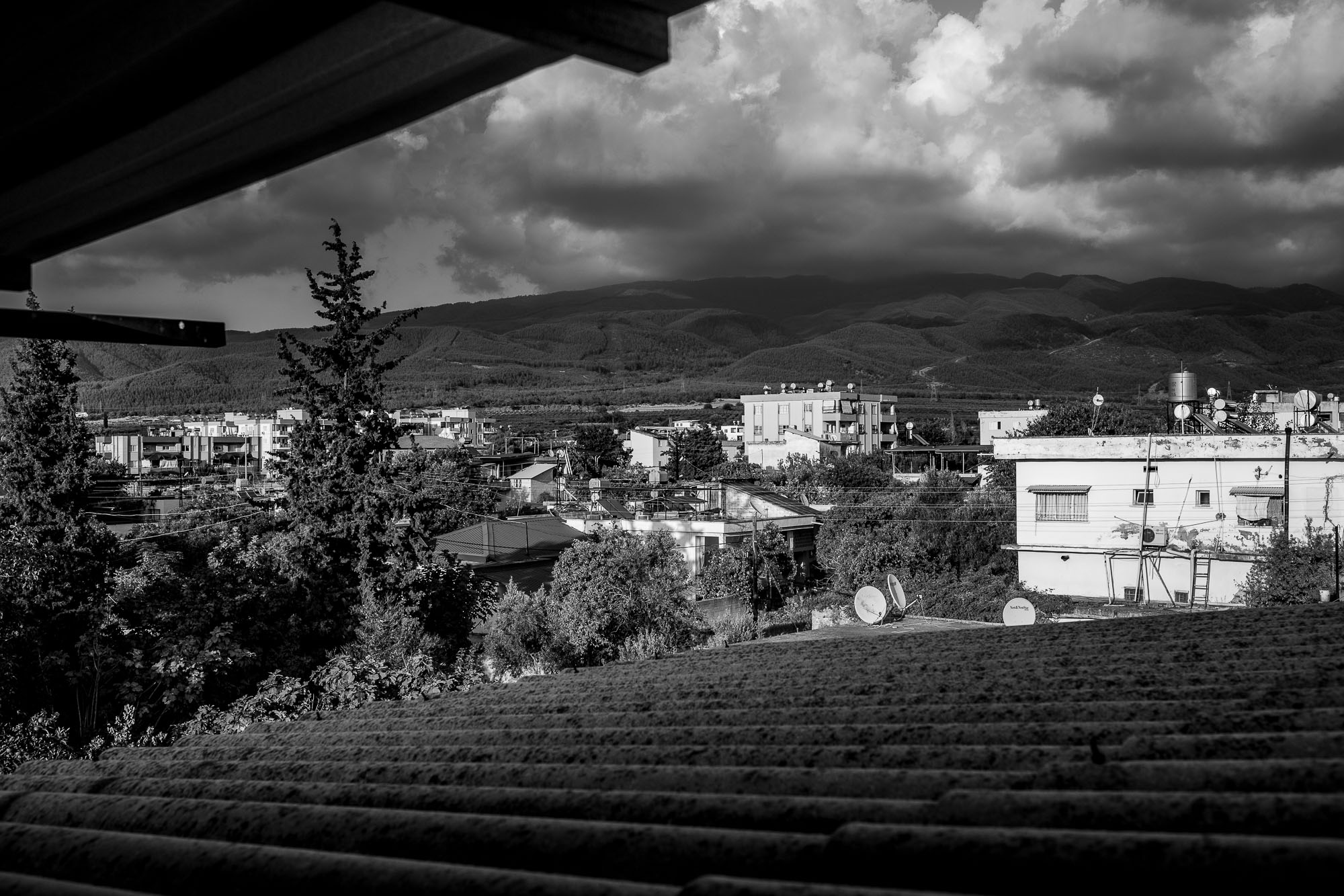 Houses, trees, mountains, seen from just under the roof