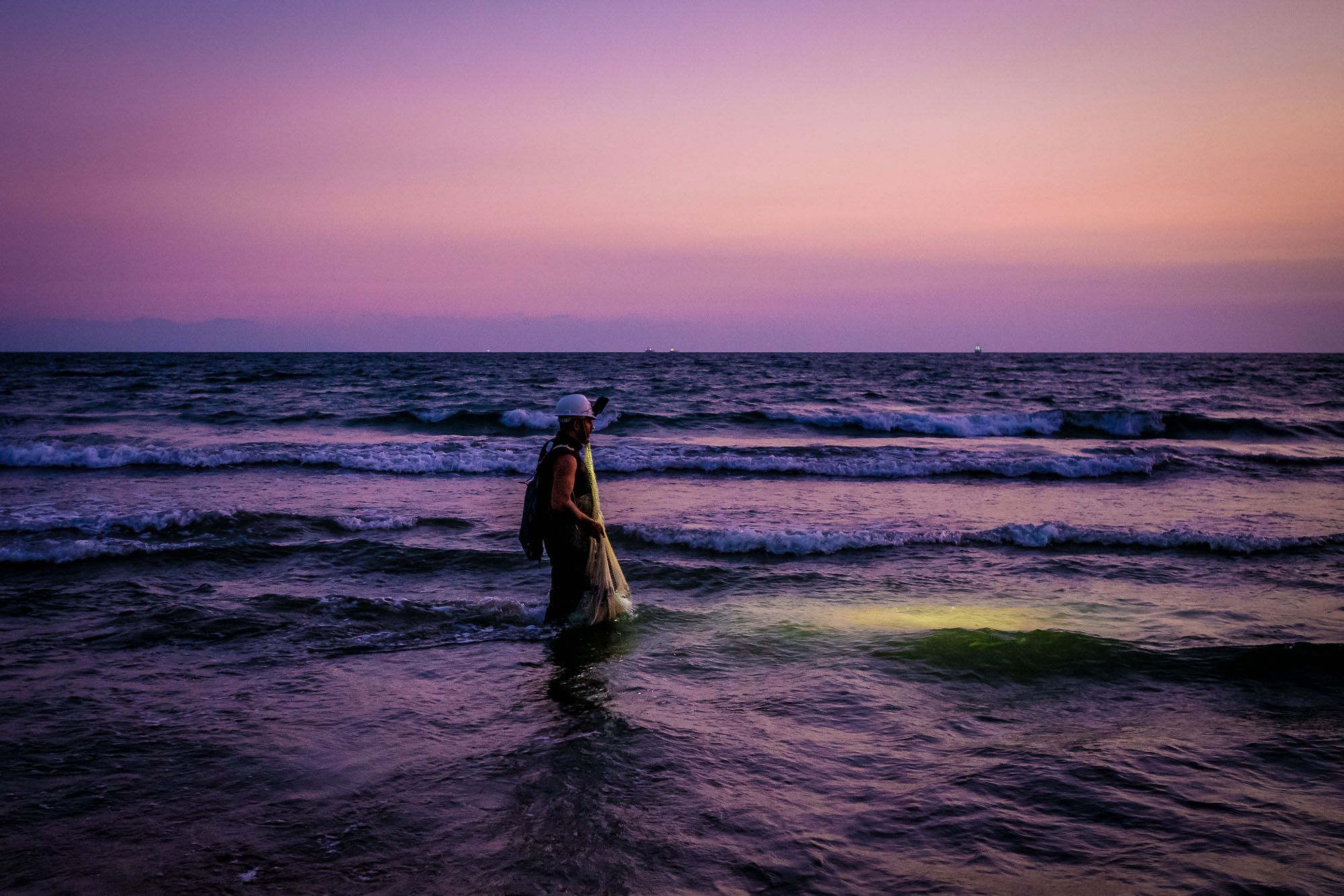 Fisherman walking in shallow water scanning for fish with his head lamp