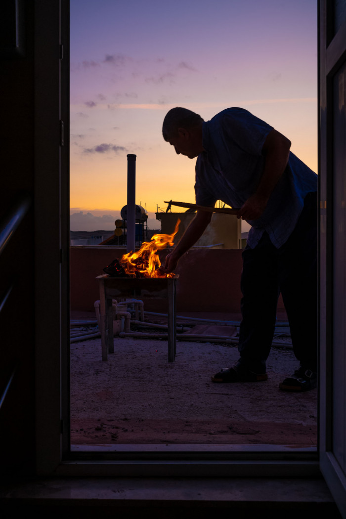 Silhouetted man starting a grill fire on the rooftop, purple sunset sky in the background