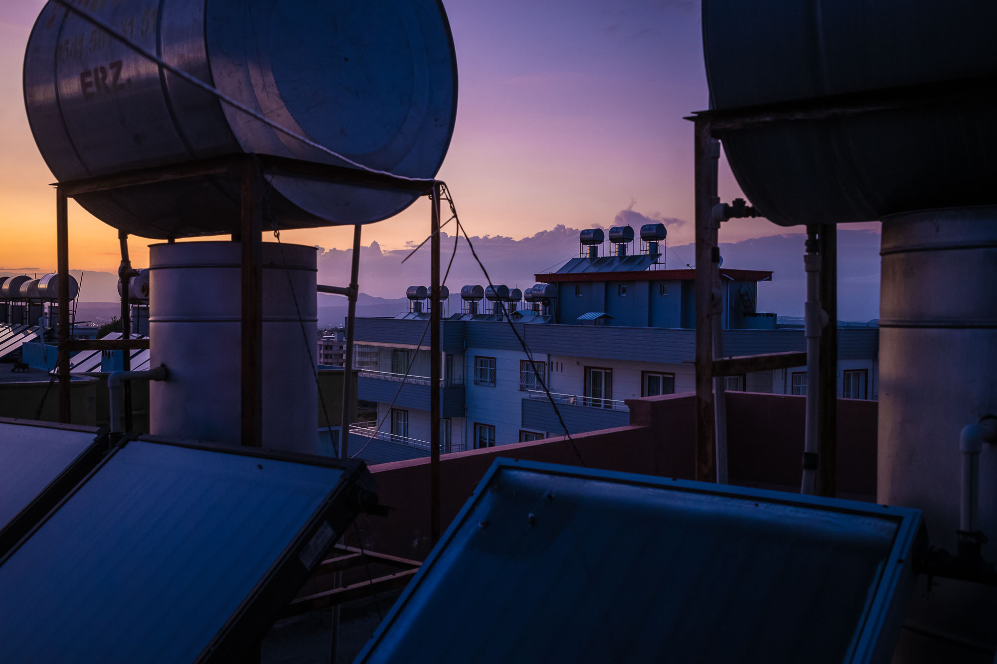 Rooftop filled with solar hear units, purple, sunset sky in the background