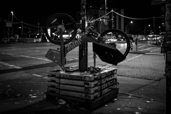 An upside down rental bike sits on top of a temporary traffic light
