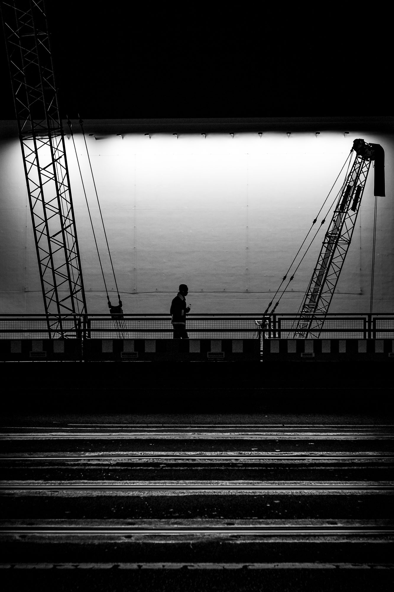 A silhouetted figure walks in front of a brighly illuminated white wall, with two cranes on either side