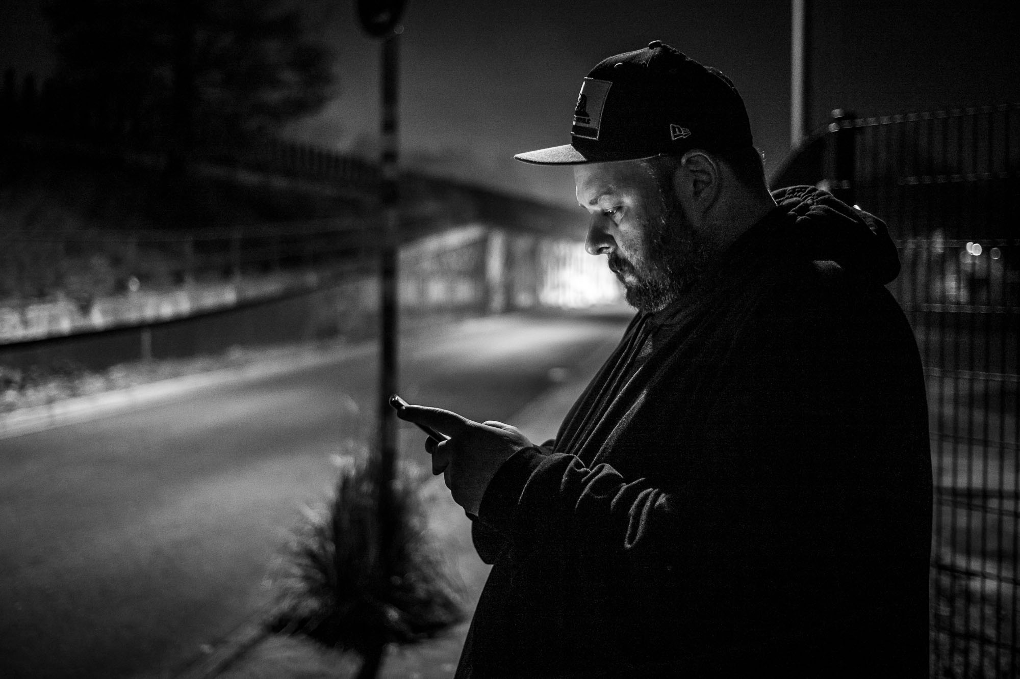 Pepo, on a street at night, illuminated by his phone