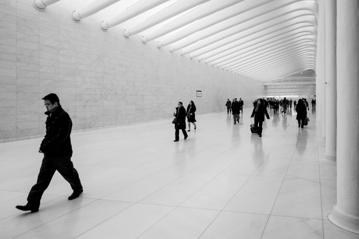 People walking along white marble wall and floor