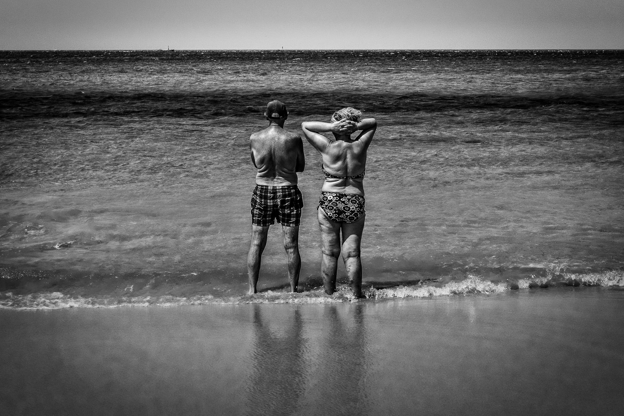 Old couple in their bathing suits, standing on the beach with their feet in the ocean