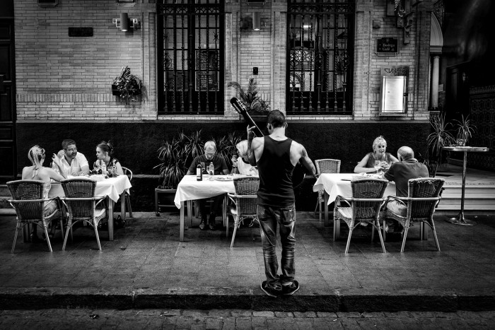 A guitarist is playing for people seated at a restaurant in the streets of Seville