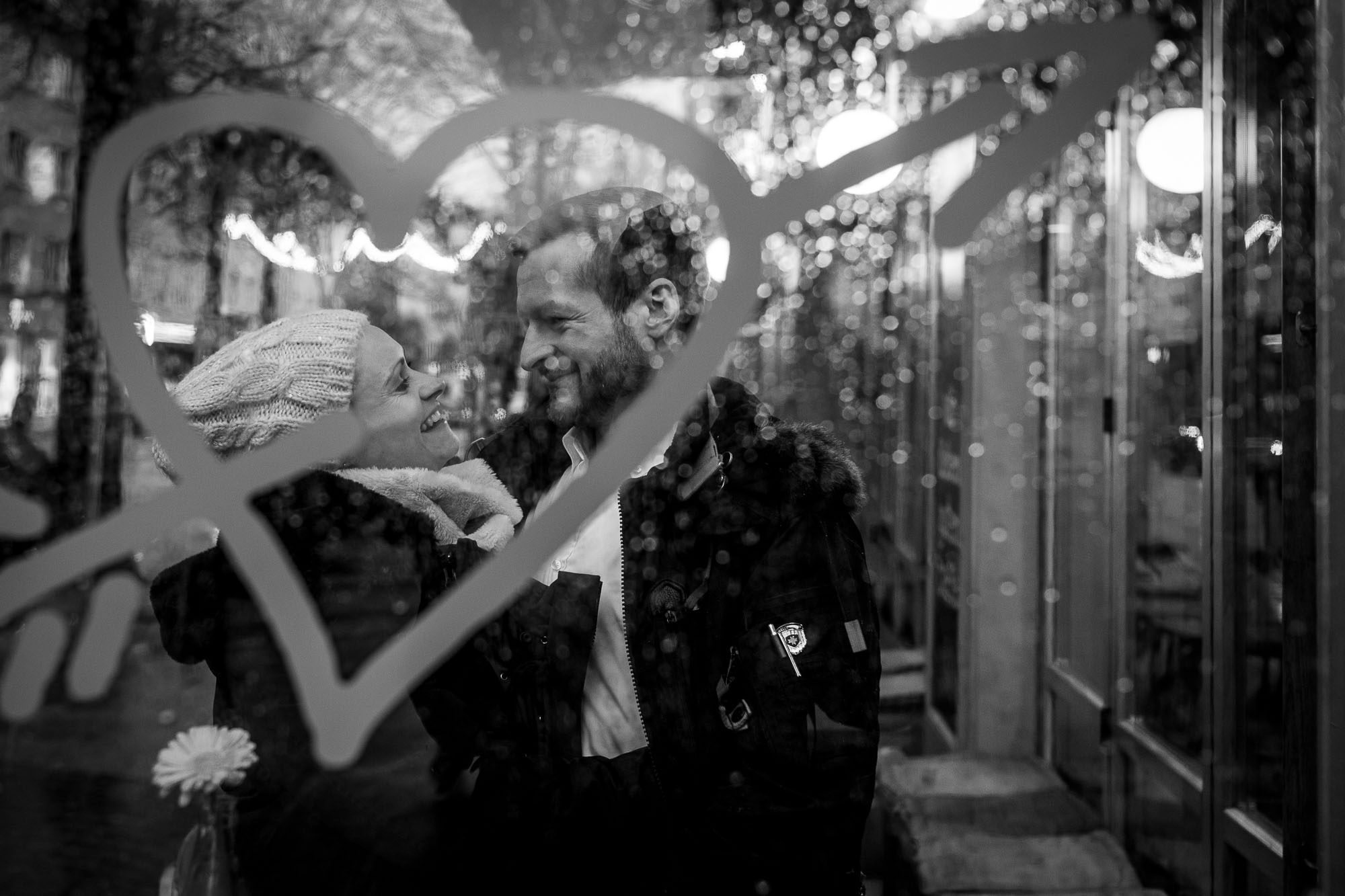 Couple about to kiss, behind a window coverd with raindrops