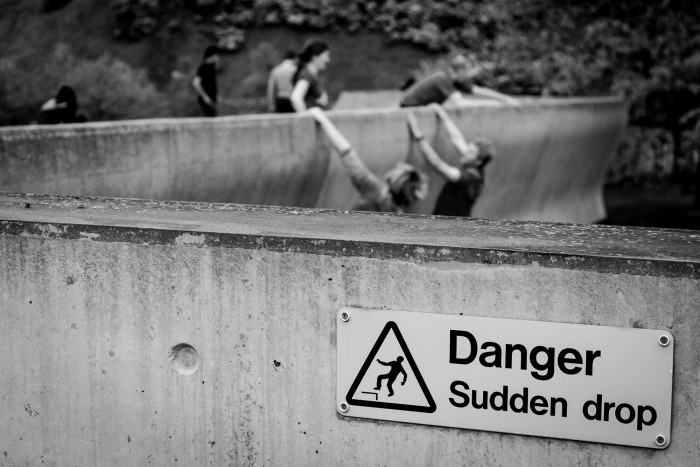 Parkour runners seen hanging off a wall with a sign saying