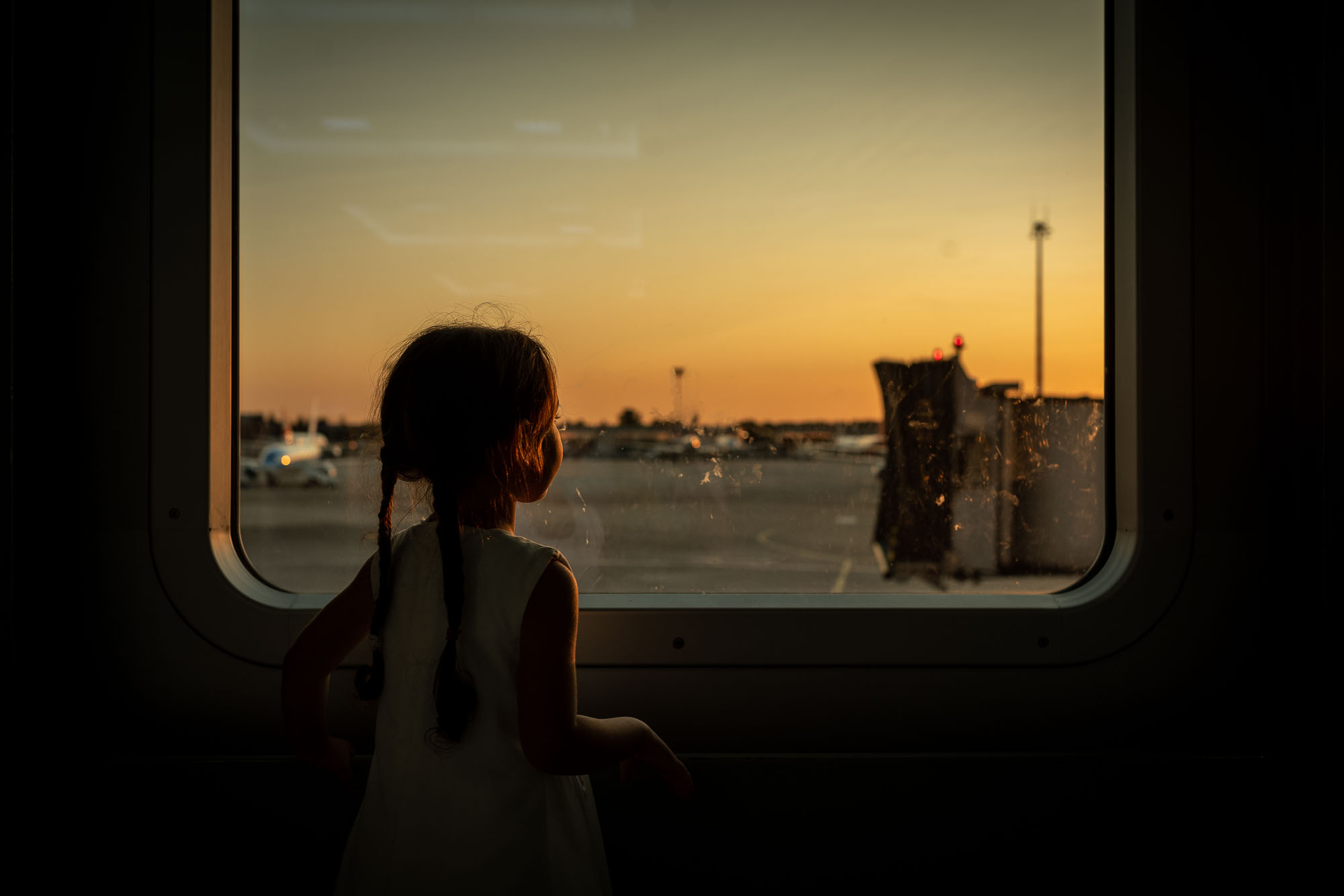 Looking out a window at the airport during sunset