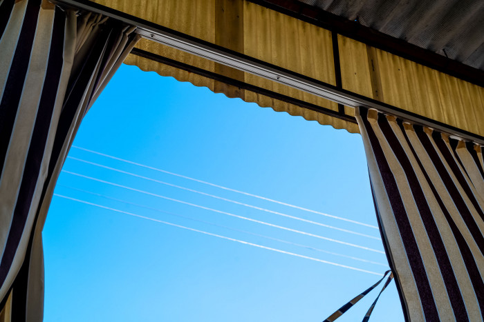 Curtains that protect the patio against the mid-day heat sway in the wind