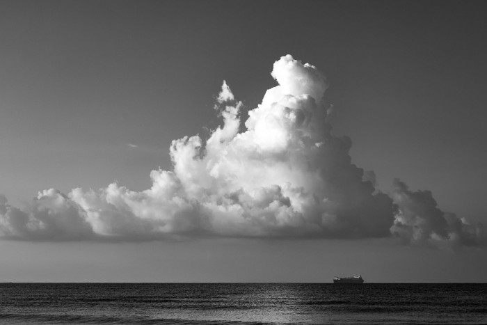 Huge cloud over a ship in the ocean in the far distance