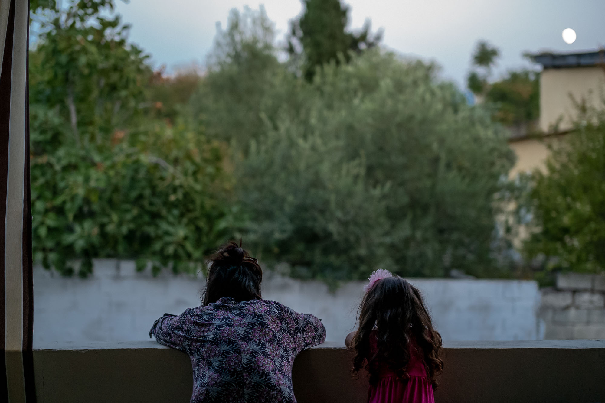 Mother and daughter looking over a wall