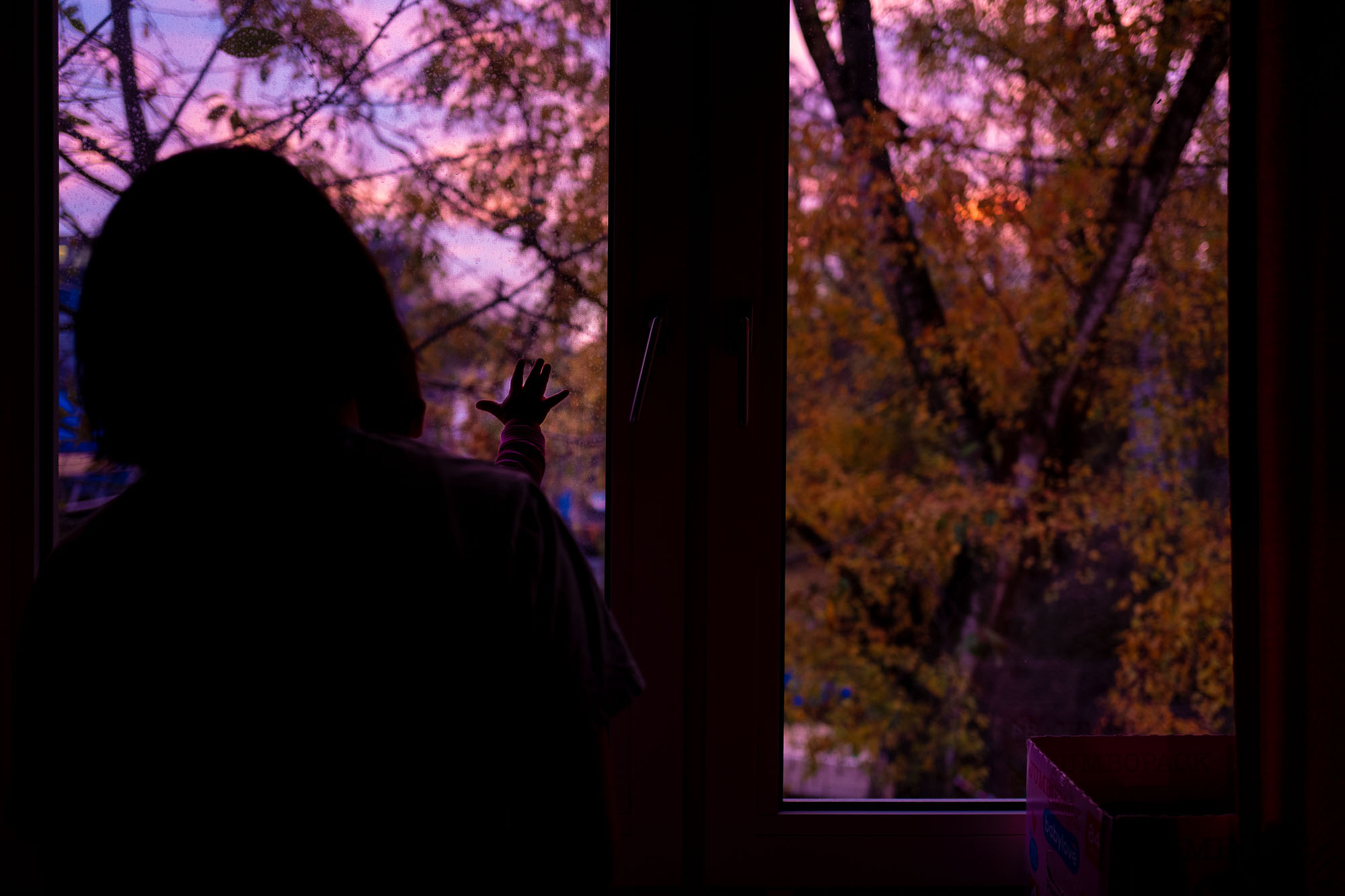 Ulya and Suvi looking out the window at a colorful sunrise