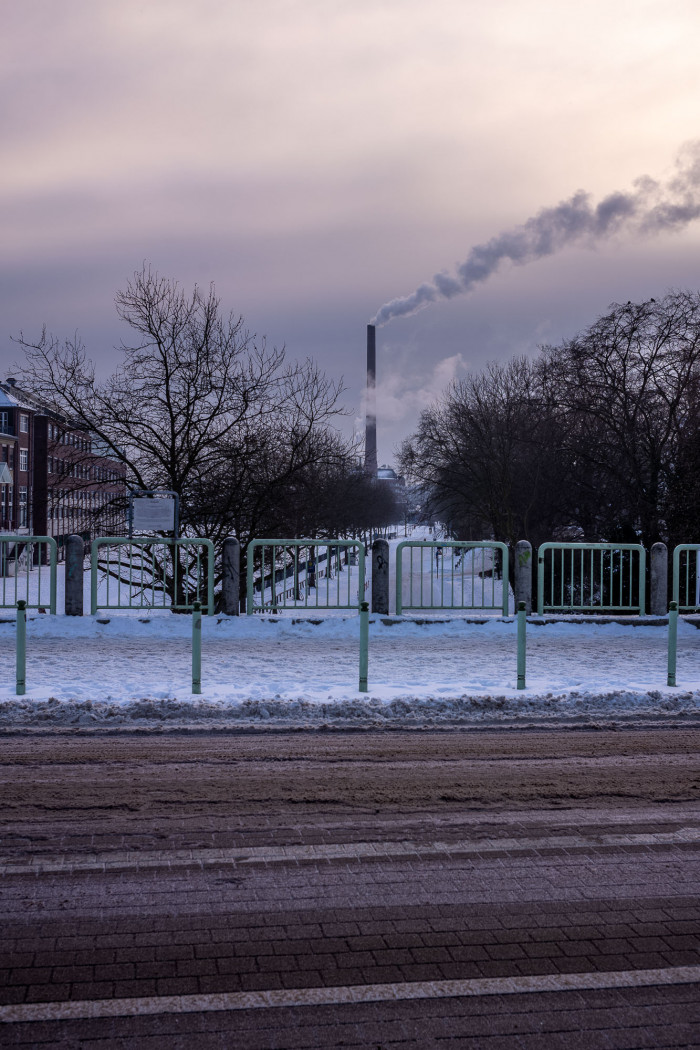 Street and snow covered sidewalk in the foreground, trees and a large chimney with smoke plume in the background