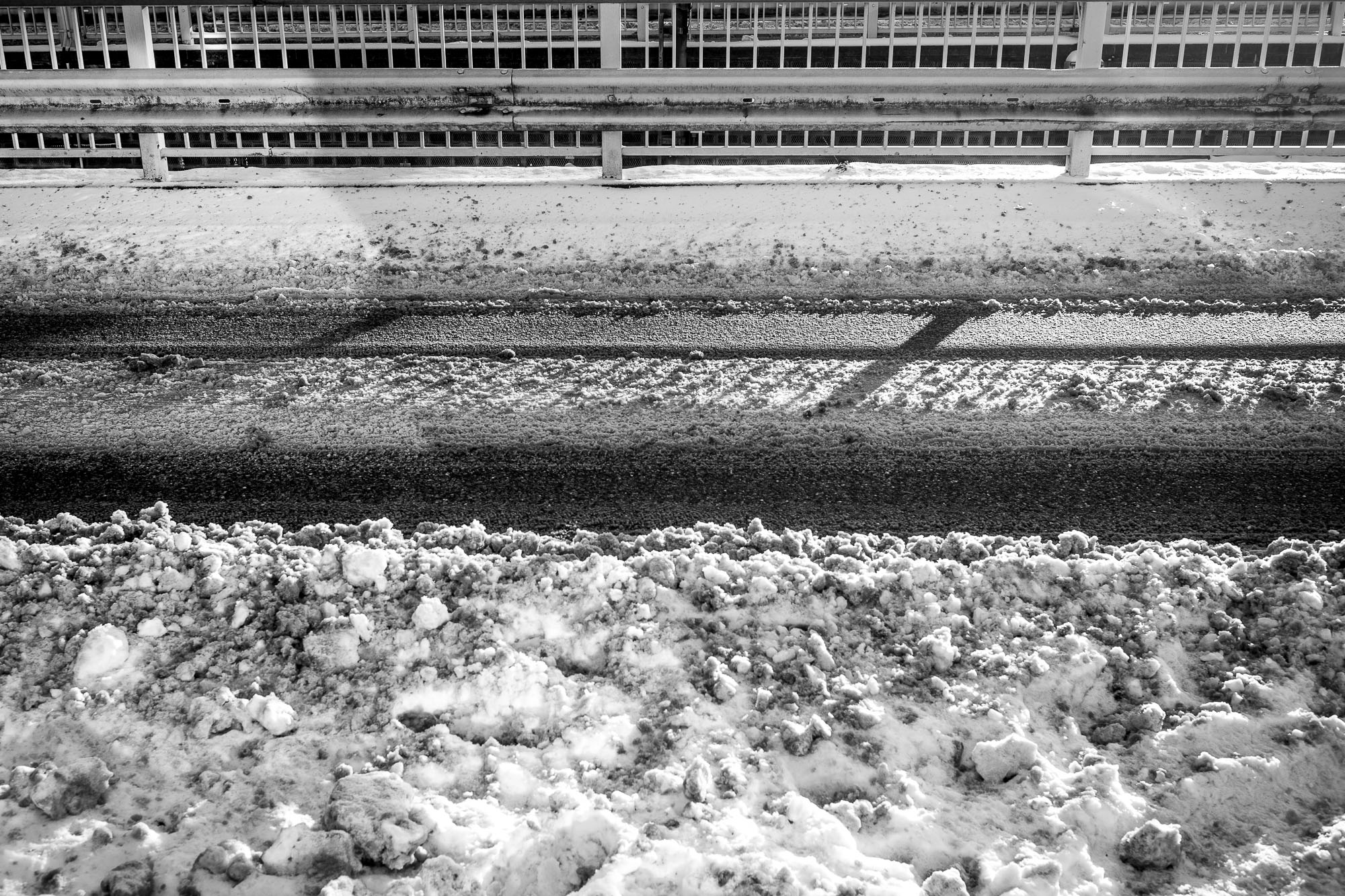 Snow covered street with tire tracks and a railing running in parallel in the background