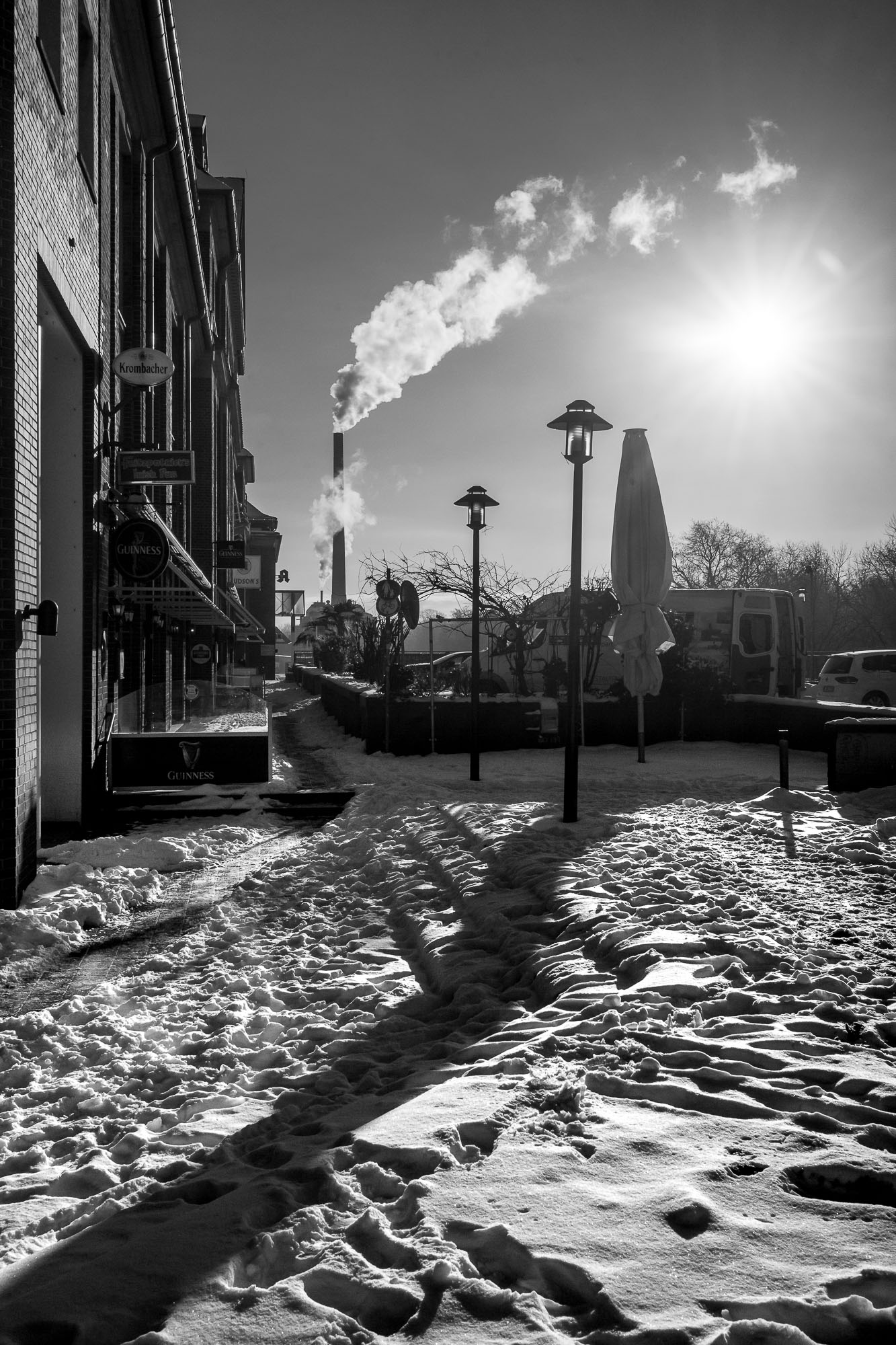 Snow covered square infront of a smoking chimney and a clear sky with the sun coming up