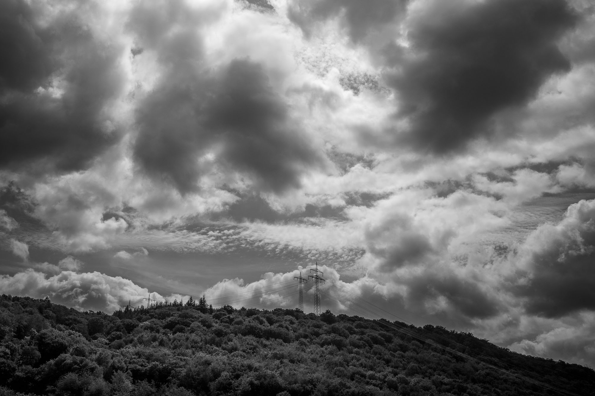 Electrical towers peak out from a wooded hill with a dramatic cloud cover above