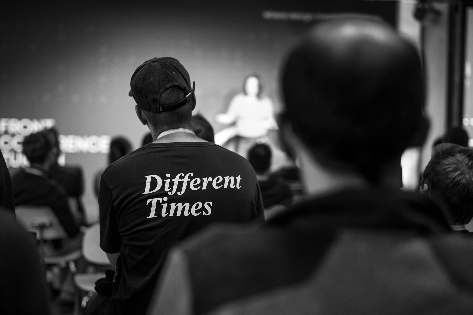 An attendee in the audience at Front Conference 2021 wears a t-shirt with a print on the back that say