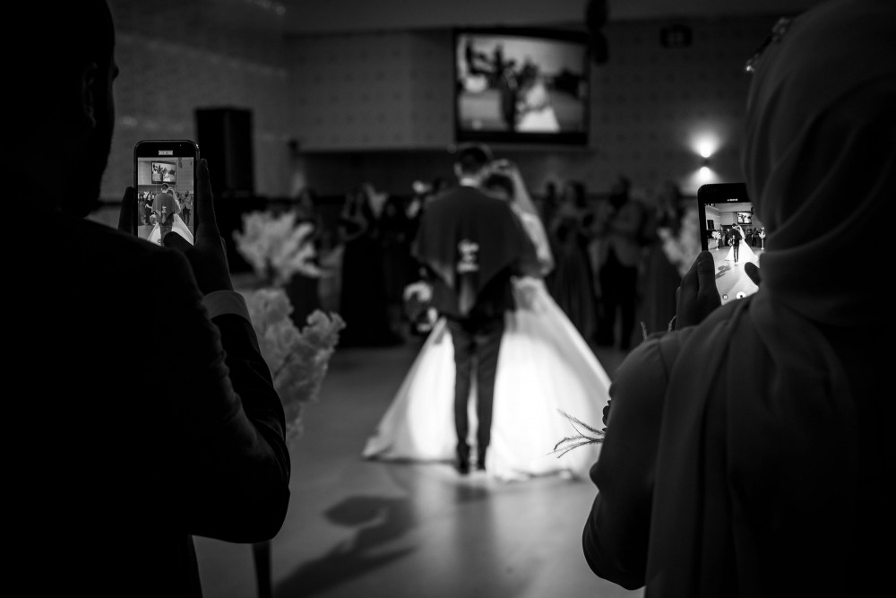 Bride and groom are dancing while guests are taking pictures with their smart phones
