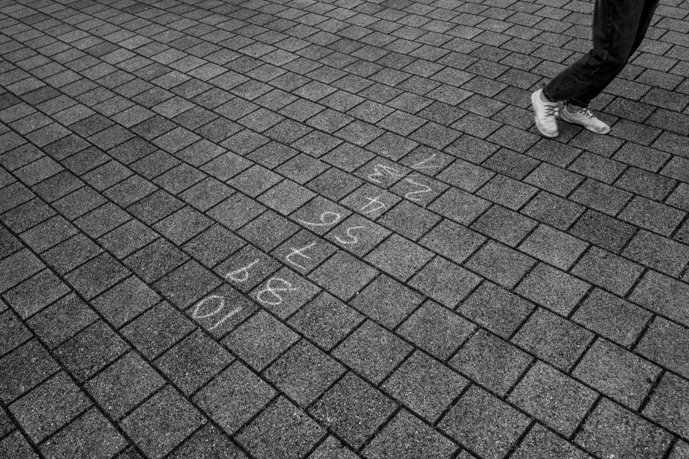 Numbers 1 to 10 written on the street with chalk and the feet of a person running by