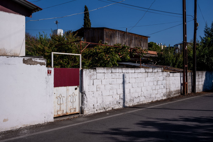 Street in Erzin, white wall with a red door