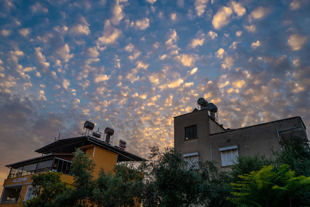 Two houses beneath a sky full of puffy clouds, illumated by the setting sun.